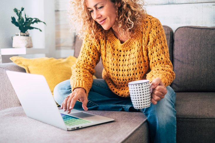 A woman drinks from a coffee mug and types on a laptop computer keyboard while sitting on her living room sofa at home